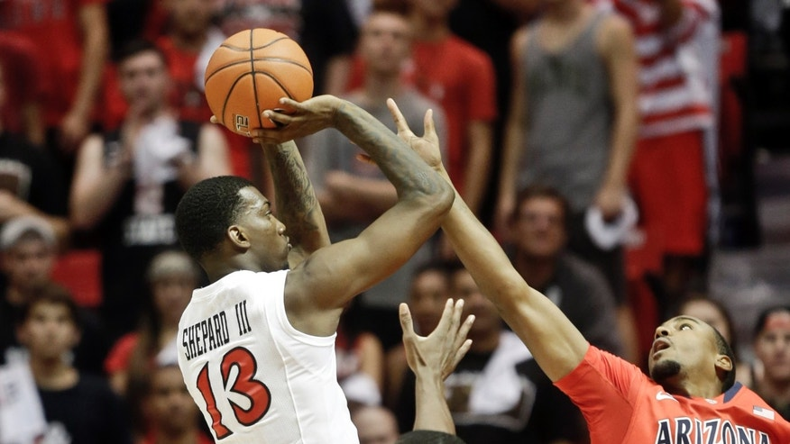 San Diego State forward Winston Shepard, left, shoots over Arizona guard Jordin Mayes during the first half of an NCAA college basketball game Thursday, Nov. 14, 2013, in San Diego. (AP Photo/Lenny Ignelzi)