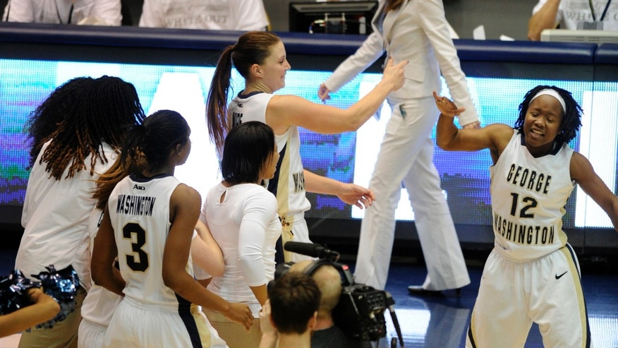 George Washington guard Megan Nipe, top center, celebrates a 75-72 win over California with teammate Danni Jackson (12) and others at an NCAA college basketball game on Friday, Nov. 15, 2013, in Washington. (AP Photo/Nick Wass)