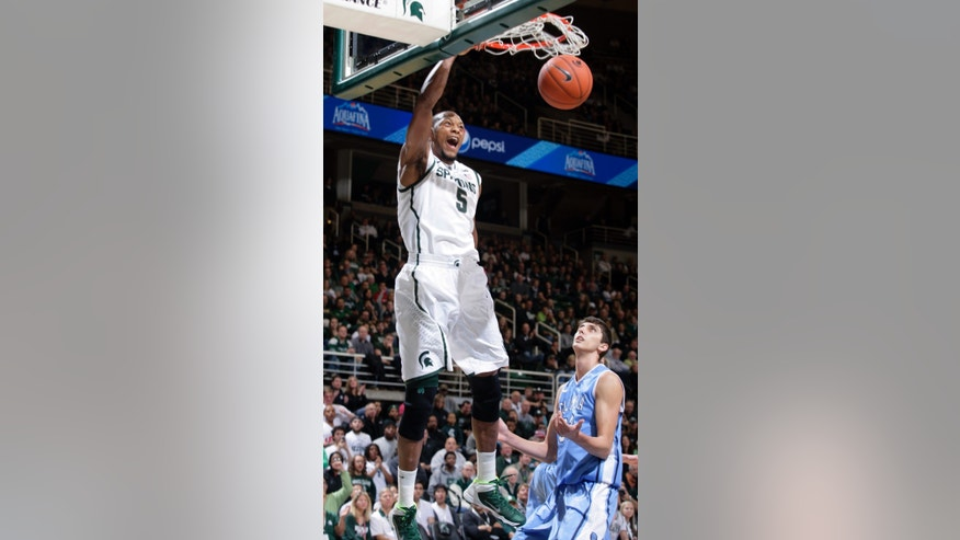 Michigan State's Adreian Payne (5) dunks over Columbia's Luke Petrasek during the first half of an NCAA college basketball game Friday, Nov. 15, 2013, in East Lansing, Mich. (AP Photo/Al Goldis)