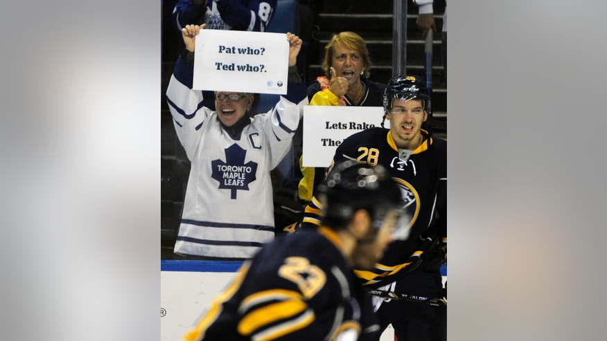 A Toronto Maple Leafs fan holds up a sign during the pregame skate before an NHL hockey game against the Buffalo Sabres in Buffalo, N.Y., Friday, Nov. 15, 2013. (AP Photo/Gary Wiepert)
