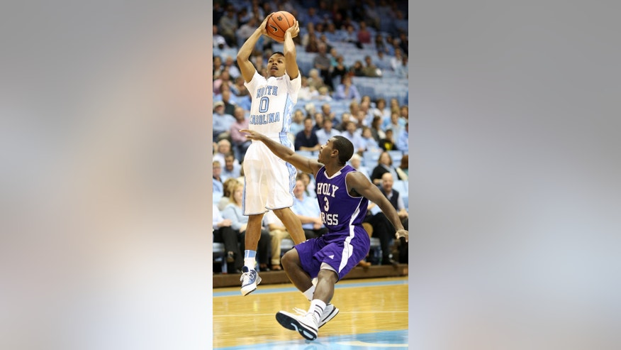 North Carolina's Nate Britt (0) shoots over Holy Cross' Justin Burrell during the first half of their NCAA college basketball game in Chapel Hill, N.C., Friday, Nov.15, 2013. (AP Photo/Erik Perel)