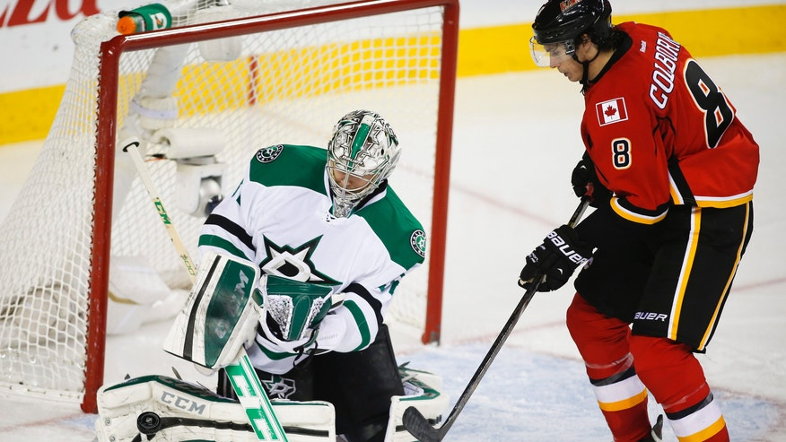 Dallas Stars goalie Kari Lehtonen, left, from Finland, kicks away a shot form Calgary Flames' Joe Colborne during third period NHL hockey action in Calgary, Alberta, Thursday, Nov. 14, 2013. The Dallas Stars beat the Calgary Flames 7-3. (AP Photo/The Canadian Press, Jeff McIntosh)