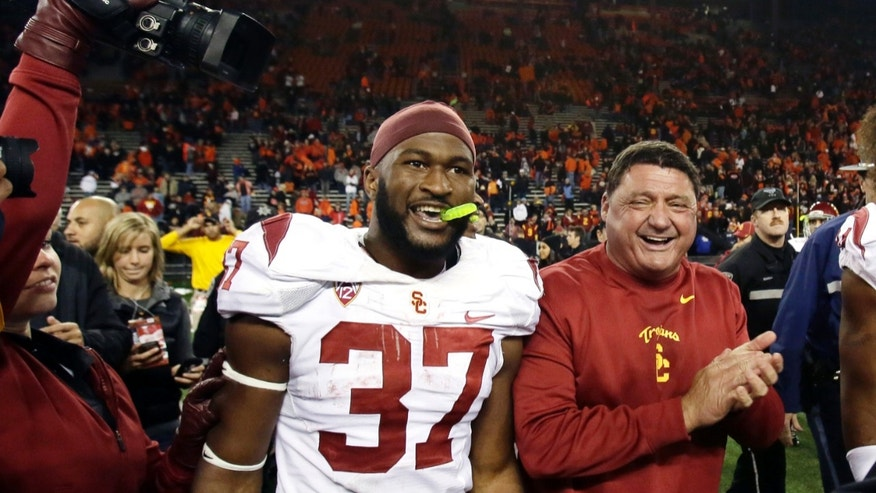 FILE - In this Nov. 1, 2013, file photo, Southern California interim football coach Ed Orgeron, right, celebrates with running back Javorius Allen after their 31-14 win over Oregon State in an NCAA college football game in Corvallis, Ore. Orgeron has injected fun back into USC, and victories have followed. The Trojans' 4-1 resurgence under their interim coach leads them into a Coliseum visit from No. 5 Stanford, which is two wins away from the chance to host the Pac-12 title game. (AP Photo/Don Ryan, File)