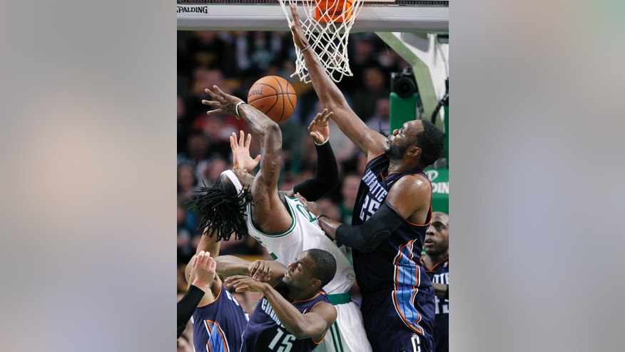 Boston Celtics small forward Gerald Wallace, top left, has his shot blocked going up against Charlotte Bobcats center Al Jefferson, right, and guard Kemba Walker (15) in the second half of an NBA basketball game in Boston, Wednesday, Nov. 13, 2013. The Bobcats won 89-83. (AP Photo/Elise Amendola)