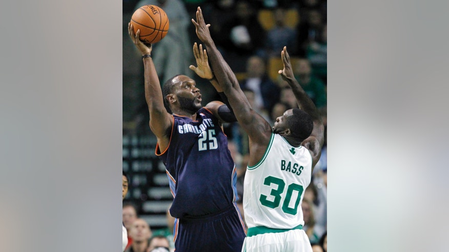 Charlotte Bobcats center Al Jefferson (25) shoots as Boston Celtics power forward Brandon Bass defends in the first quarter of an NBA basketball game in Boston, Wednesday, Nov. 13, 2013. (AP Photo/Elise Amendola)
