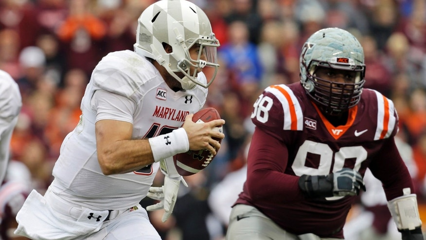 Maryland quarterback C.J. Brown (16) turns the corner for a good run as Virginia Tech defensive tackle Derrick Hopkins (98) pursues during the first half of an NCAA college football game in  Blacksburg, Va., Saturday, Nov. 16, 2013.   (AP Photo/Steve Helber)