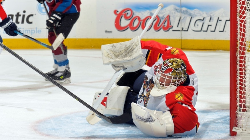 Florida Panthers goalie Tim Thomas makes a save against the Colorado Avalanche during the first period of an NHL hockey game on Saturday, Nov. 16, 2013, in Denver. (AP Photo/Jack Dempsey)