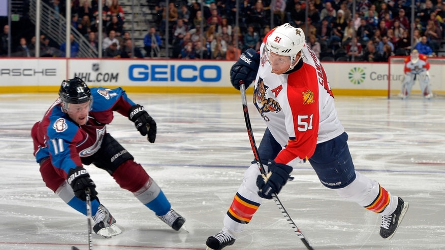 Florida Panthers defenseman Brian Campbell (51) shoots a goal against Colorado Avalanche left wing Jamie McGinn (11) during the second period of an NHL hockey game, on Saturday, Nov. 16, 2013, in Denver. (AP Photo/Jack Dempsey)