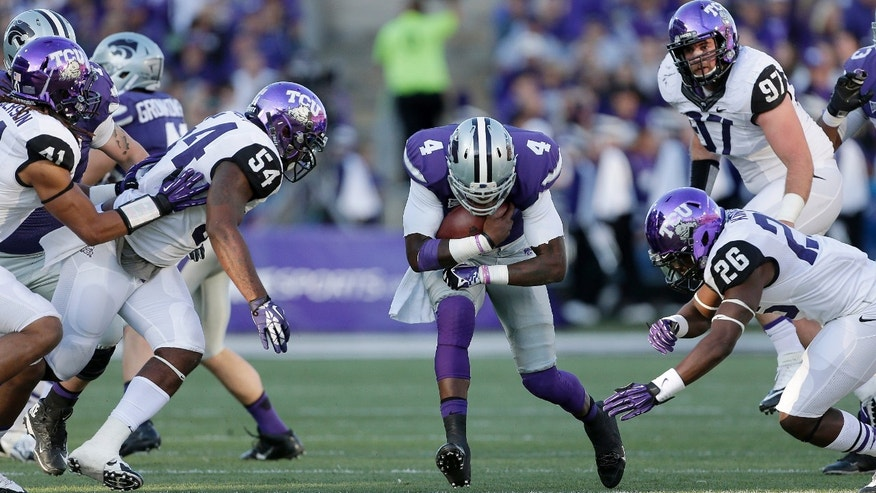 Kansas State quarterback Daniel Sams (4) gets past TCU defenders Jonathan Anderson (41), Marcus Mallet (54), Derrick Kindred (26) and Jon Koontz (97) to run for a first down during the first half of an NCAA college football game Saturday, Nov. 16, 2013, in Manhattan, Kan. (AP Photo/Charlie Riedel)
