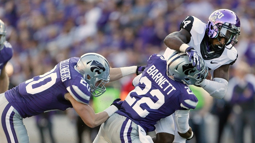 TCU wide receiver David Porter, right, is tackled by Kansas State defensive backs Dante Barnett (22) and Dylan Schellenberg during the first half of an NCAA college football game Saturday, Nov. 16, 2013, in Manhattan, Kan. (AP Photo/Charlie Riedel)