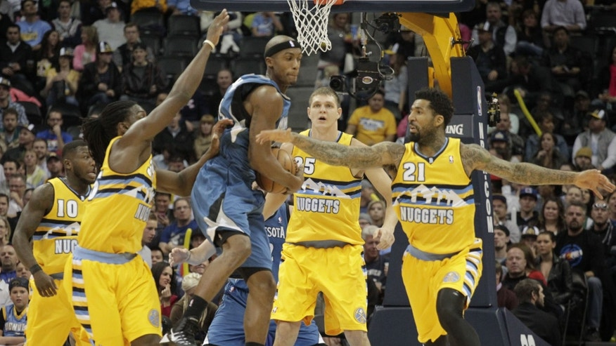 Minnesota Timberwolves forward Corey Brewer, third from left, scoops up a loose ball against Denver Nuggets forwards Kenneth Faried (35) and Wilson Chandler (21) as Nuggets center Timofey Mozgov (25) backs up the play during the first quarter of an NBA basketball game in Denver, Friday, Nov. 15, 2013. (AP Photo/Joe Mahoney)