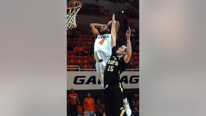 Arkansas-Pine Bluff's Trent Whiting (15) defends on a dunk by Oklahoma State wing Brian Williams (4) during the first half of an NCAA college basketball game in Stillwater, Okla., Friday, Nov. 15, 2013. (AP Photo/Brody Schmidt)