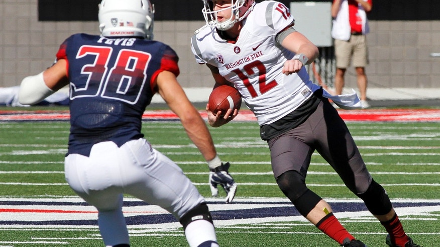 Washington State's quarterback Connor Holiday (12) runs for a short gain before being tackled by Arizona's Jared Tevis (38) in the first half of an NCAA college football game on Saturday, Nov. 16, 2013, in Tucson, Ariz. (AP Photo/John MIller)