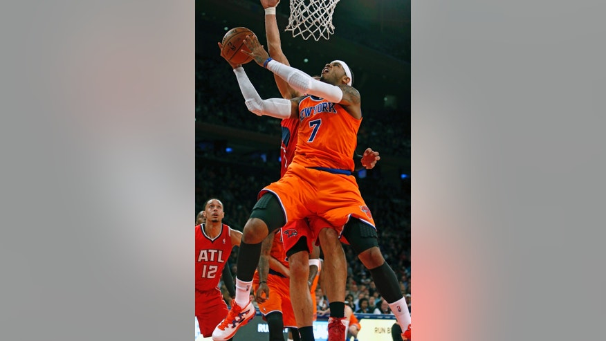 New York Knicks' Carmelo Anthony (7) shoots against Atlanta Hawks' Gustavo Ayon, behind, during the first half of an NBA basketball game Saturday, Nov. 16, 2013, in New York. (AP Photo/Jason DeCrow)