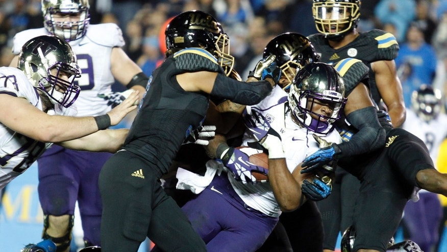 Washington wide receiver Damore'ea Stringfellow, center,  scores a 14-yard touchdown against UCLA in the fourth quarter of their NCAA college football game Friday, Nov. 15, 2013, in Pasadena, Calif. UCLA won the game 41-31. (AP Photo/Alex Gallardo)