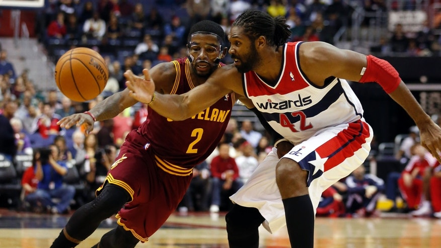 Washington Wizards forward Nene (42), from Brazil, slaps the ball away from Cleveland Cavaliers guard Kyrie Irving (2) in the first half of an NBA basketball game on Saturday, Nov. 16, 2013, in Washington. (AP Photo/Alex Brandon)