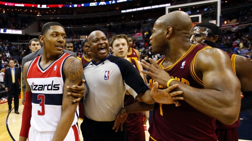 Washington Wizards guard Bradley Beal (3) and Cleveland Cavaliers guard Jarrett Jack (1) are separated by a referee after an NBA basketball game on Saturday, Nov. 16, 2013, in Washington. The Cavaliers won 103-96 in overtime. (AP Photo/Alex Brandon)