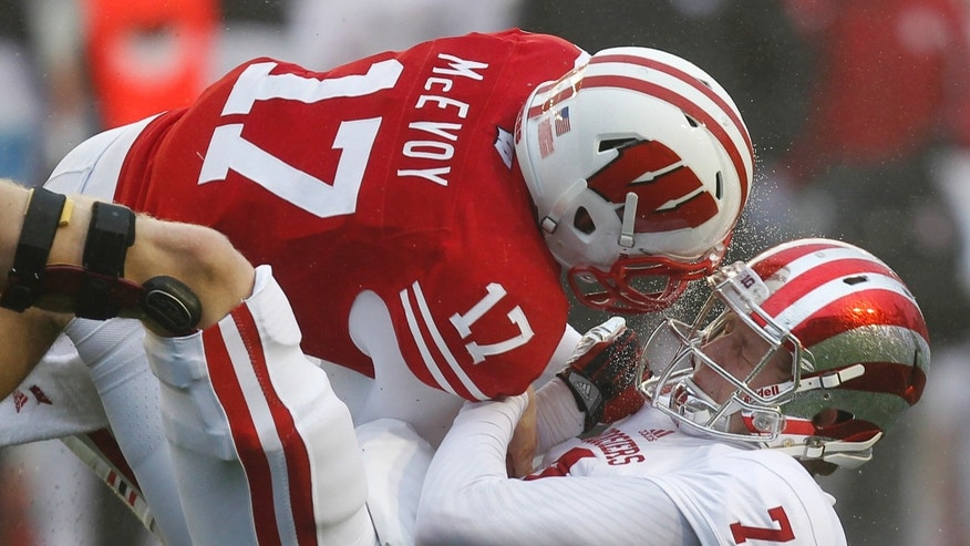 Indiana quarterback Nate Sudfeld (7) fumbles against Wisconsin's Tanner McEvoy during the first half of a college football game Saturday, Nov. 16, 2013, in Madison, Wis. Indiana recovered the fumble. (AP Photo/Andy Manis)