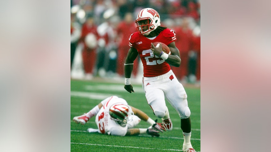 Wisconsin's James White runs against Indiana's Brandon Grubble during the second half of an NCAA college football game, Saturday, Nov. 16, 2013, in Madison, Wis. White had 208 yards in Wisconsin's 51-3 win.  (AP Photo/Andy Manis)