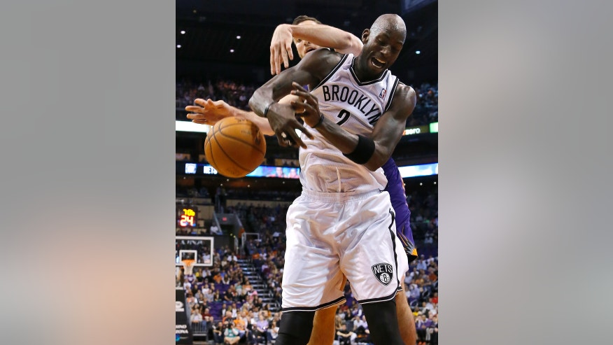 Phoenix Suns' Miles Plumlee, rear, and Brooklyn Nets' Kevin Garnett battle for the ball during the first half of an NBA game, Friday, Nov. 15, 2013, in Phoenix. (AP Photo/Matt York)