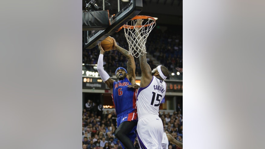 Detroit Pistons forward Josh Smith, left, goes to the basket against Sacramento Kings center DeMarcus Cousins during the first quarter of an NBA basketball game in Sacramento, Calif., Friday, Nov. 15, 2013. (AP Photo/Rich Pedroncelli)