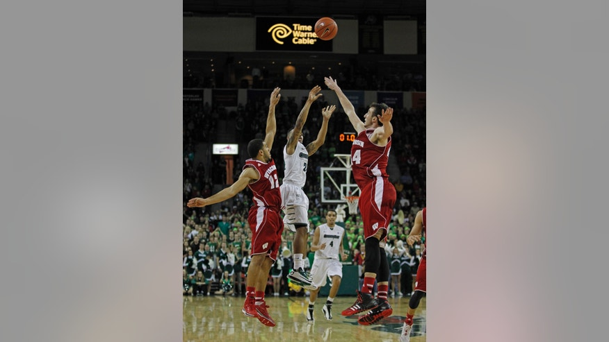 Green Bay's Keifer Sykes shoots a last-second ball to try to tie the game while guarded by Wisconsin's Traevon Jackson (12) and Frank Kaminsky (44) during the second half of an NCAA college basketball game on Saturday, Nov. 16, 2013, in Green Bay, Wis. Wisconsin won 69-66. (AP Photo/Matt Ludtke)