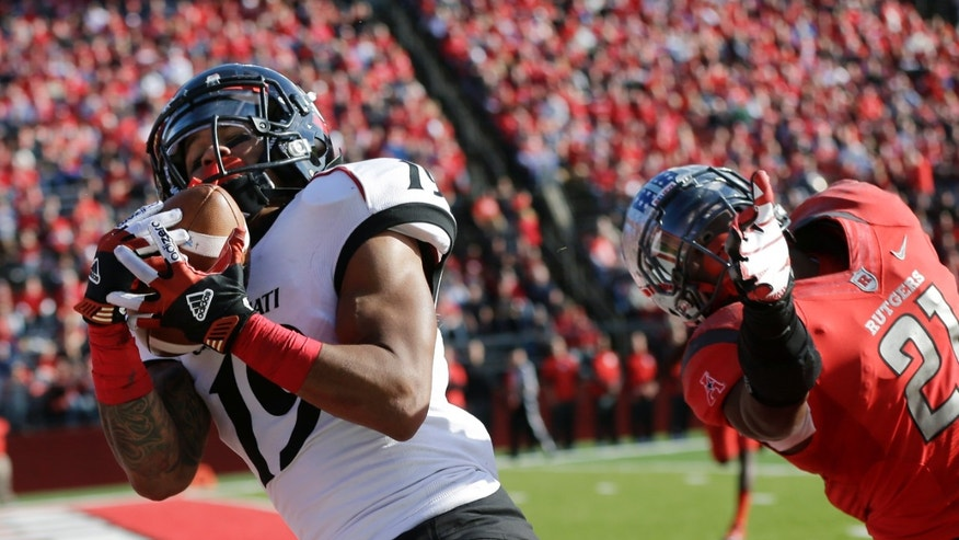 Cincinnati wide receiver Shaq Washington (19) catches a pass for a touchdown in front of Rutgers defensive back Lorenzo Waters  (21) during the first half of an NCAA college football game in Piscataway, N.J., Saturday, Nov. 16, 2013.   (AP Photo/Mel Evans)