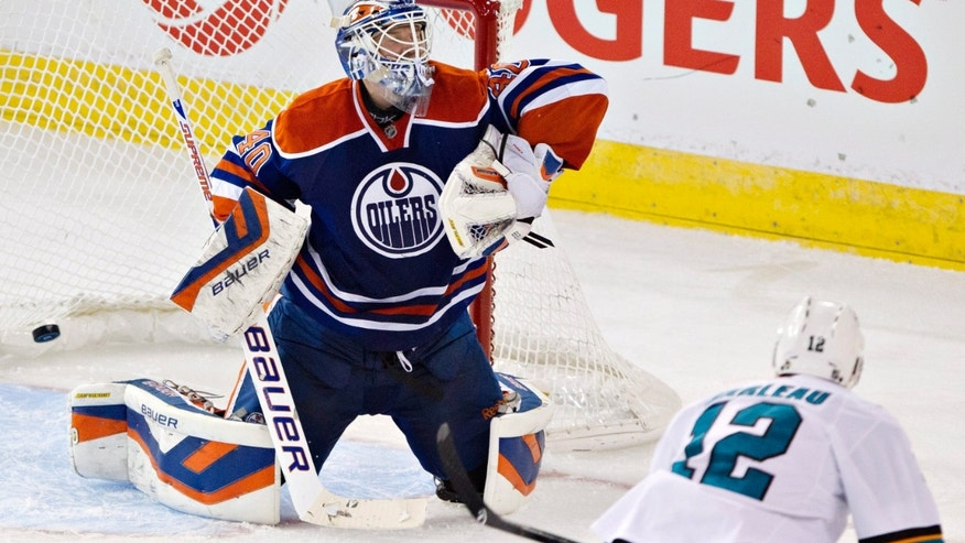 San Jose Sharks' Patrick Marleau (12) scores a goal on Edmonton Oilers' Devan Dubnyk (40) during the second period of an NHL hockey game Friday, Nov. 15, 2013, in Edmonton, Alberta. (AP Photo/The Canadian Press, Jason Franson)