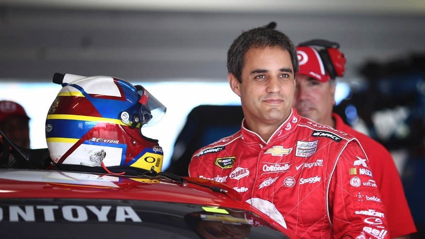 Driver Juan Pablo Montoya, of Colombia, climbs into for practice for Sunday's NASCAR Sprint Cup series auto race Friday, Nov. 15, 2013, at Homestead-Miami Speedway in Homestead, Fla. (AP Photo/J Pat Carter)