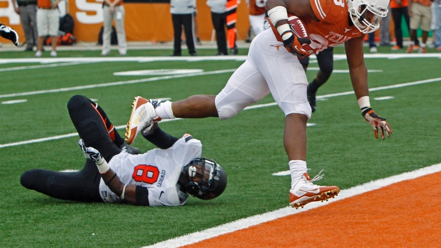 Texas running back Malcolm Brown (28) scores a touchdown against Oklahoma State safety Daytawion Lowe (8) during the second quarter of an NCAA college football game Saturday, Nov. 16, 2013, in Austin, Texas. (AP Photo/Michael Thomas)