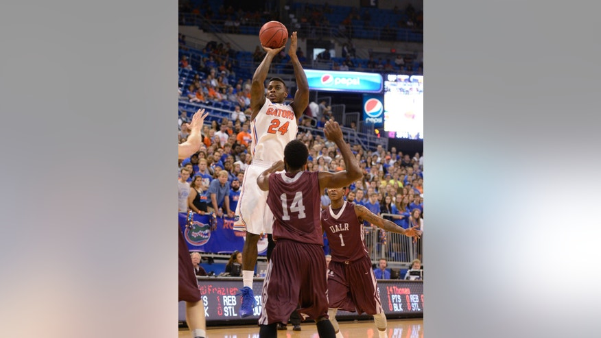 Florida forward Casey Prather (24) goes up for a shot in front of Arkansas-Little Rock guard J.T. Thomas (14)  during the first half of an NCAA college basketball game Saturday, Nov. 16, 2013, in Gainesville, Fla. (AP Photo/Phil Sandlin)