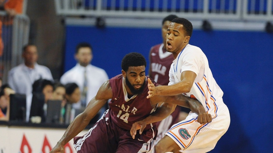 Arkansas-Little Rock guard J.T. Thomas (14) tries to get around Florida's Kasey Hill (0) during the first half of an NCAA college basketball game Saturday, Nov. 16, 2013, in Gainesville, Fla. (AP Photo/Phil Sandlin)