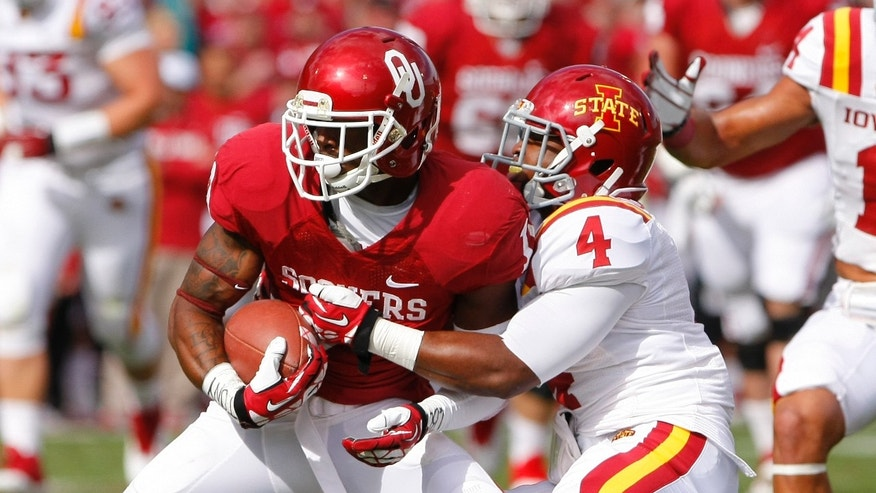 Oklahoma wide receiver Lacoltan Bester is tackled by Iowa State's Sam Richardson in the second quarter of an NCAA college football game in Norman, Okla., on Saturday, Nov. 16, 2013.  (AP Photo/Alonzo Adams)