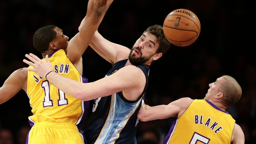 Memphis Grizzlies' Marc Gasol, center, of Spain, loses the ball as he is defended by Los Angeles Lakers' Wesley Johnson, left, and Steve Blake during the first half of an NBA basketball game on Friday, Nov. 15, 2013, in Los Angeles. (AP Photo/Jae C. Hong)