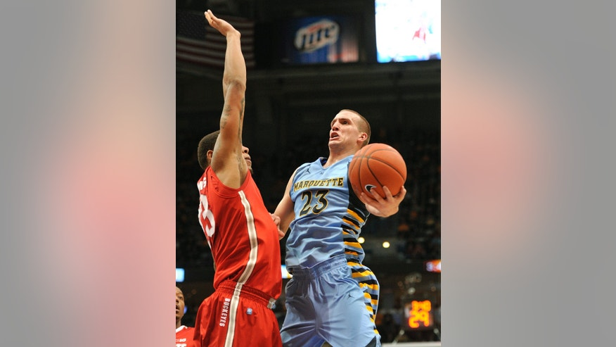 Ohio State's' Amir Williams, left, defends as Marquette's 's Jake Thomas (23) drives to the basket during the first half of an NCAA college basketball game, Saturday, Nov. 16, 2013, in Milwaukee. (AP Photo/Jim Prisching)