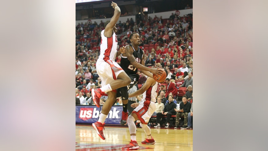Omaha guard Justin Simmons, center, drives between UNLV forward Jamal Aytes, left, and guard Kendall Smith during their NCAA college basketball game on Friday, Nov. 15, 2013, in Las Vegas. (AP Photo/Las Vegas Sun, Sam Morris) LAS VEGAS REVIEW JOURNAL OUT