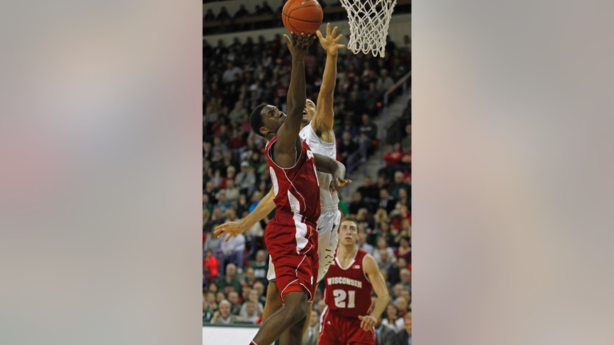 Wisconsin's Nigel Hayes, left, drives the lane past Green Bay's Kenneth Lowe during the second half of an NCAA college basketball game on Saturday, Nov. 16, 2013, in Green Bay, Wis. Wisconsin won 69-66. (AP Photo/Matt Ludtke)