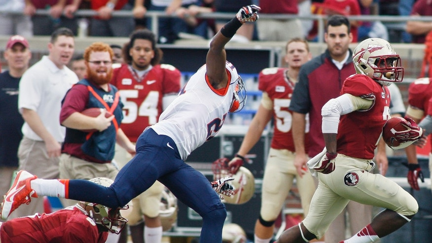 Florida State quarterback Jameis Winston, left,  (5) throws a block to take out Syracuse cornerback Julian Whigham (21), allowing running back Kermit Whitfield (7) to score a 74-yard touchdown in the first quarter of an NCAA college football game on Saturday, Nov. 16, 2013, in Tallahassee, Fla. (AP Photo/Phil Sears)