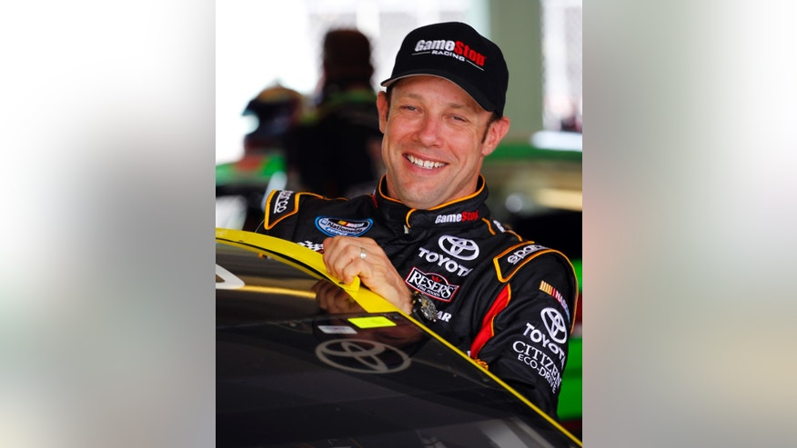 Driver Matt Kenseth smiles as he climbs into his car for during practice for Sunday's NASCAR Sprint Cup series auto race at the Homestead-Miami Speedway, Saturday, Nov. 16, 2013, in Homestead, Fla. (AP Photo/Terry Renna)