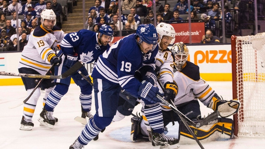 Toronto Maple Leafs Joffrey Lupul (19) battles for the puck with Buffalo Sabres Henrik Tallinder as Sabres goalie Jhonas Enroth, right, looks on during the second period of an NHL hockey game, Saturday, Nov. 16, 2013 in Toronto. (AP Photo/The Canadian Press, Chris Young)