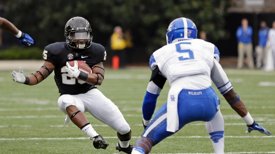 Vanderbilt running back Brian Kimbrow (25) gets past Kentucky safety Ashely Lowery (5) as Kimbrow runs 21-yards for a touchdown in the first quarter of an NCAA college football game on Saturday, Nov. 16, 2013, in Nashville, Tenn. (AP Photo/Mark Humphrey)