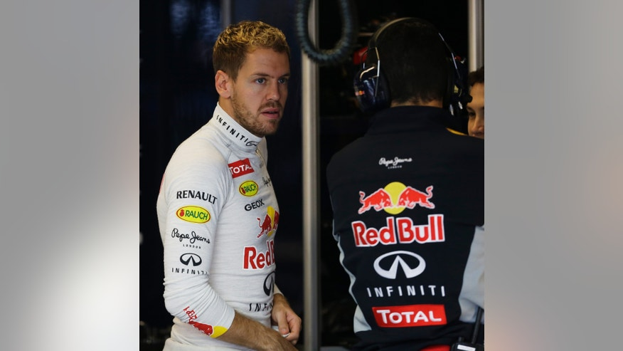Red Bull driver Sebastian Vettel of Germany gets talks to a crew member before the third practice session for the Formula One U.S. Grand Prix auto race at the Circuit of the Americas, Saturday, Nov. 16, 2013, in Austin, Texas. (AP Photo/Darron Cummings)