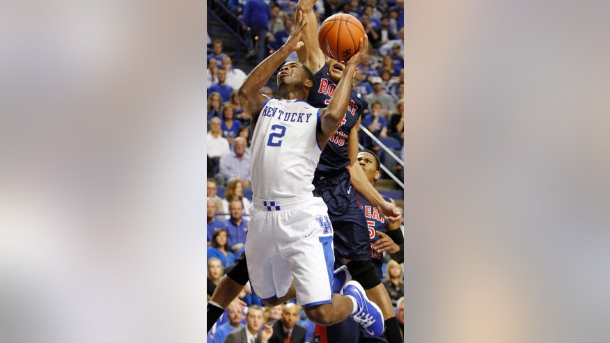Kentucky's Aaron Harrison (2) shoots under pressure from Robert Morris' Aaron Tate during the first half of an NCAA college basketball game Sunday, Nov. 17, 2013, in Lexington, Ky. (AP Photo/James Crisp)