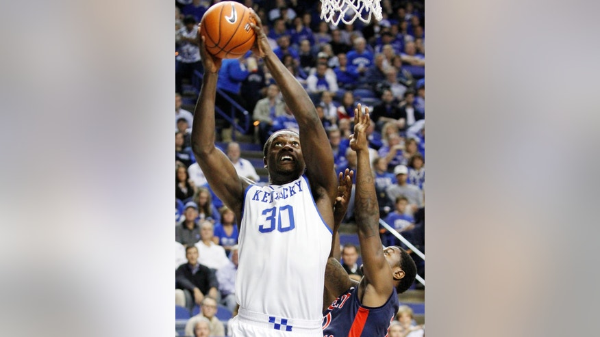 Kentucky's Julius Randle (30) shoots next to Robert Morris' Desjuan Newton during the first half of an NCAA college basketball game Sunday, Nov. 17, 2013, in Lexington, Ky. (AP Photo/James Crisp)
