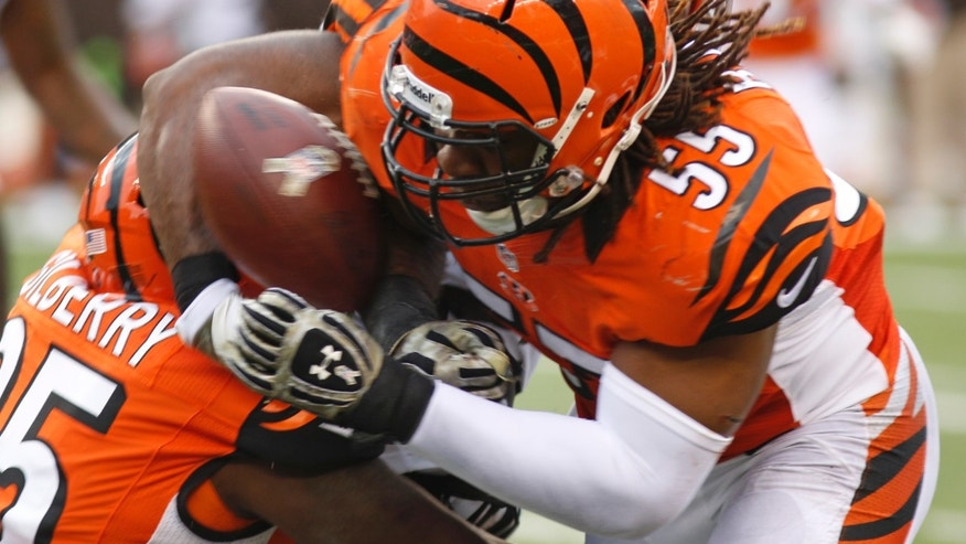 Cincinnati Bengals outside linebacker Vontaze Burfict (55) knocks the ball loose from Cleveland Browns running back Chris Ogbonnaya in the first half of an NFL football game on Sunday, Nov. 17, 2013, in Cincinnati. Burfict recovered the fumble and ran it into the end zone for a touchdown. (AP Photo/David Kohl)