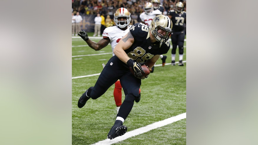 New Orleans Saints tight end Josh Hill (89) scores on a touchdown reception in front of San Francisco 49ers strong safety Donte Whitner in the first half of an NFL football game in New Orleans, Sunday, Nov. 17, 2013. (AP Photo/Bill Haber)