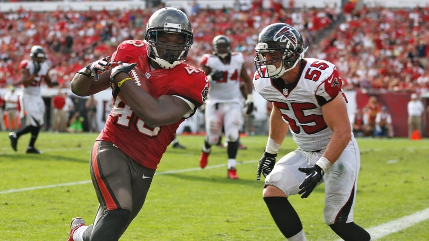 Tampa Bay Buccaneers running back Bobby Rainey (43) scores past Atlanta Falcons outside linebacker Paul Worrilow (55) on a 4-yard touchdown reception during the third quarter of an NFL football game on Sunday, Nov. 17, 2013, in Tampa, Fla. (AP Photo/Reinhold Matay)