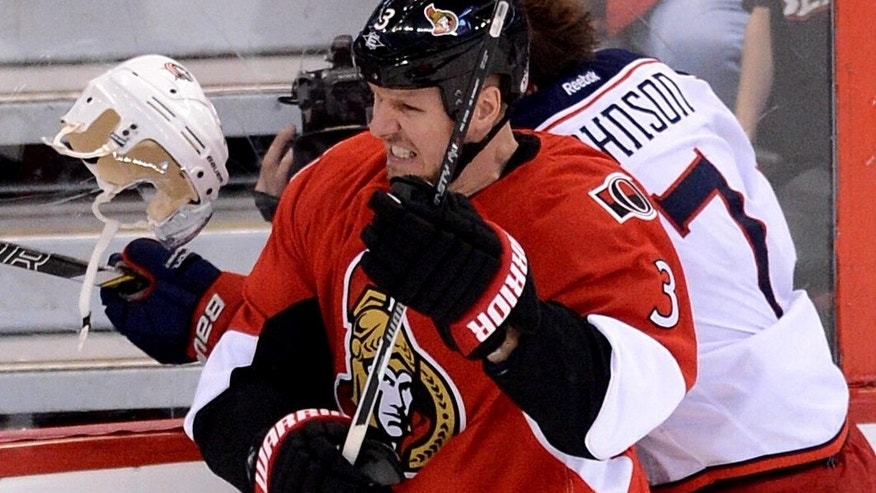 Ottawa Senators' Marc Methot, left,  checks Columbus Blue Jackets' Jack Johnson during second period NHL hockey action in Ottawa, Ontario, on Sunday, Nov. 17, 2013. (AP Photo/The Canadian Press, Sean Kilpatrick)