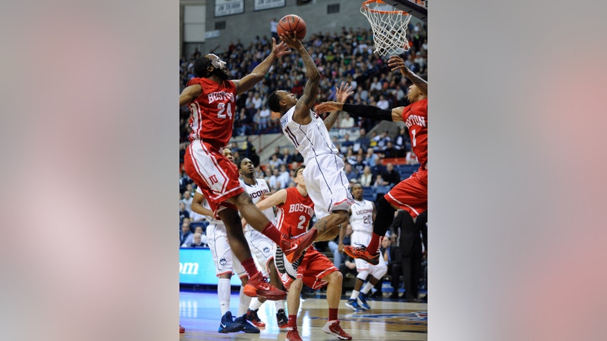 Connecticut's Ryan Boatright (11) drives past Boston University's Travis Robinson (24) and Maurice Watson Jr. (1) during the first half of an NCAA college basketball game in Storrs, Conn., on Sunday, Nov. 17, 2013. (AP Photo/Fred Beckham)