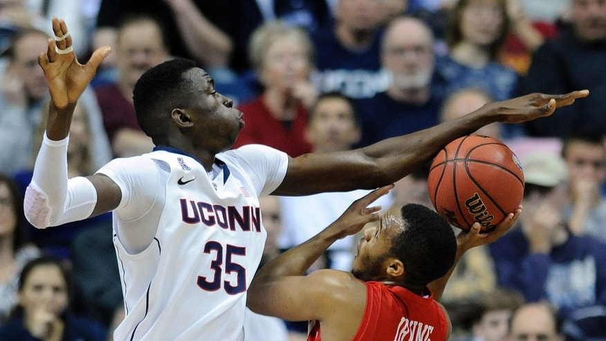 Connecticut's Amida Brimah (35) attempts to block the shot of Boston University's D.J. Irving (13) during the first half of an NCAA college basketball game in Storrs, Conn., on Sunday, Nov. 17, 2013. (AP Photo/Fred Beckham)